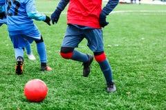 Heathy pojke för ung aktiv sport i den röda och blåa sportswearen som kör och sparkar en röd boll på fotbollfält royaltyfri foto