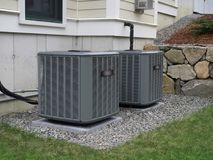 Heating and air conditioning units. In back of a residential house stock image