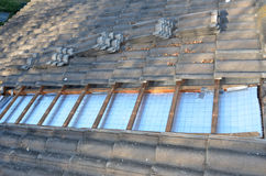Heating Bills. Installing roof insulation in a home to reduce heat wastage and heating bills, and help reduce global warming Royalty Free Stock Image