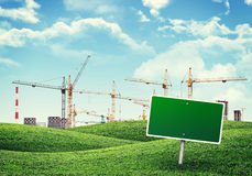 Heating and building cranes over green hills. Stock Images
