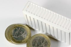 Heating costs. White radiator with euro coins Royalty Free Stock Photography