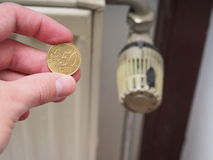 Heating costs (50 euro cent version). 50 euro cent coin infront of a radiator, for concepts like small heating costs, savings potential and small inflation in Royalty Free Stock Photo