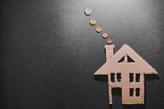 Heating costs. Euro coins coming out of the chimney of a cardboard house for your heating costs concepts - copy space to the left Royalty Free Stock Photos