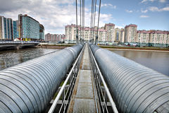 Heating duct crosses river on cable-stayed bridge in residential Royalty Free Stock Images
