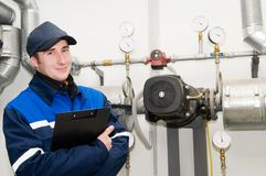 Heating engineer in boiler room. Glad maintenance engineer checking technical data of heating system equipment in a boiler room Stock Image