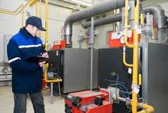 Heating engineer in boiler room. Maintenance engineer checking technical data of heating system equipment in a boiler room