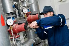 Heating engineer in boiler room. Maintenance engineer checking technical data of heating system equipment in a boiler room Royalty Free Stock Photo