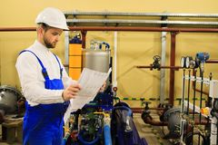 Heating engineer with drawings at industrial plant stock photo
