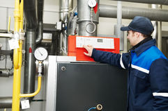 Heating engineer repairman. Maintenance engineer checking technical data of heating system equipment in a boiler house Stock Images