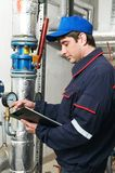 Heating engineer repairman in boiler room. Maintenance repairman engineer of heating system equipmant in a boiler house Royalty Free Stock Photography