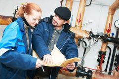 Heating engineers in boiler room Royalty Free Stock Photo