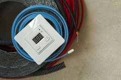 Heating floor system wires, cables and control panel. Renovation and construction concept. Comfort house. Stock Photo