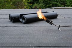 Heating and melting bitumen roofing felt Flat roof installation.  Royalty Free Stock Photos