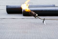Heating and melting bitumen - roofing felt Flat roof installation.  Royalty Free Stock Photography