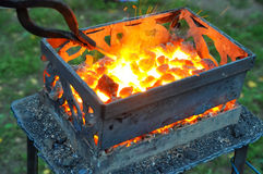Heating of the metal forging on hot coals Royalty Free Stock Photo