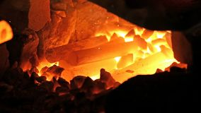 Heating of metal parts in blacksmith furnace stock footage