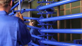 Heating painted form-work part, two men taking girders out of chamber. Stock footage stock footage