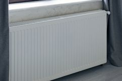 Heating panel radiator in white color installed in room. Royalty Free Stock Photography