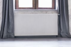 Heating radiator under the window with a wooden frame and curtains. Heating radiator under the window with wooden frame and curtains Stock Photo