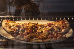 Heating ready-to eat pizza in oven Stock Image