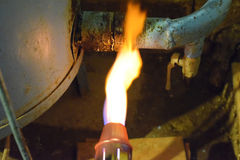 Heating a steel pipe with a blowtorch. The flame of a blowtorch Stock Image