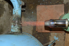 Heating a steel pipe with a blowtorch. The flame of a blowtorch Royalty Free Stock Photo