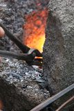 Heating the stick. A craftsman/blacksmith working metal the oldfashioned way, with hammer and anvil and open fire, using wrench to pull metal out of fire Royalty Free Stock Photos