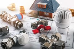 House heating system installation equipment. Heating system installation equipment on a house plan stock image