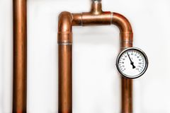 Heating system`s cooper pipes with Thermometer on a white wall Royalty Free Stock Photos