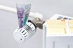 Heating thermostat with money and check Royalty Free Stock Photo