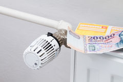Heating thermostat with money and check Royalty Free Stock Photography