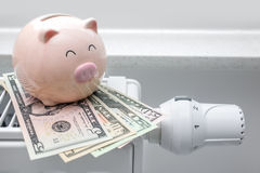 Heating thermostat with piggy bank and money. Expensive heating costs concept Stock Image