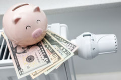Heating thermostat with piggy bank and money. Expensive heating costs concept Stock Photography
