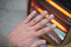 Heating up a hand. In front of an electric heater Stock Photos