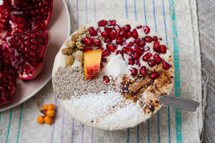 Heavegan banana smoothie with pomegranate, mulberry, coconut, Chia, carob. Raw fruit energy food. Royalty Free Stock Images