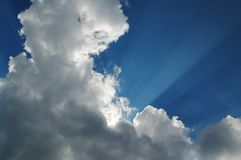 Heaven. The sun hidden behind the clouds causing the illumination of rays Royalty Free Stock Photography