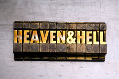 Heaven & Hell. Brass / Gold colored Heaven & Hell on silver metal background stock image