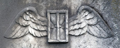 Heaven's Angel Wings. A detail from a weathered 18th century headstone.  A set of wings, and hourglass and a door are carved into the granite.  A beautiful Stock Photo