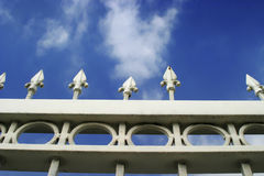 Heaven's Gate. Photo of detail of white metal gate with blue sky with white clouds and one arrow missing Stock Photos