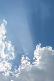 Sunbeams in Clouds. Sunbeams from behind puffy white clouds against a blue sky Stock Photo