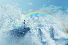 Heaven's waterfall. Young boy on a cliff looking at the horizon with a waterfall above clouds. Life journey below a rainbow in paradise. Inspirational imaginary Stock Images