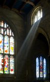 Heaven Sent. A shaft of light and stained glass windows in an English church Royalty Free Stock Image