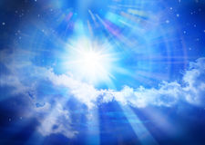 Heaven Sky Universe Sun Star Clouds Spiritual. A glowing star or sun in blue sky with shafts of light, clouds and stars Royalty Free Stock Image