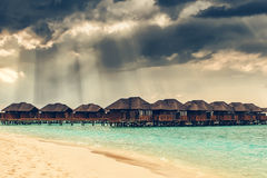 Heaven sun rays over water bungalows at tropical island Royalty Free Stock Image
