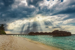 Heaven sun rays over water bungalows at tropical island Royalty Free Stock Photos