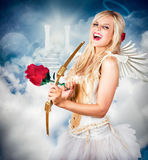 Heavenly angel of love with flower arrow. Heavenly angel of love laughing with halo on head in front of the gates of heaven. Love is the key Royalty Free Stock Photo