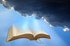 Heavenly bible spiritual light. Photo of open holy bible with sunlight rays coming through storm clouds stock photography