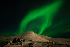 Heavenly flame. Glow of polar light over mountains Stock Images