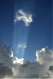 Heavenly Light. Beams from small cloud onto billowing ones below Royalty Free Stock Photo