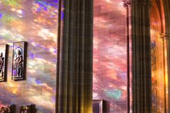 Heavenly Light. Cathedral wings with morning light glowing through stained glass windows Royalty Free Stock Photos